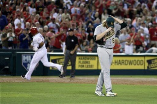 Oakland Athletics starting pitcher A.J. Griffin, right, adjusts his hat as Los Angeles Angels' Albert Pujols, background left, rounds the bases after hitting a home run during the third inning of a baseball game on Friday, July 19, 2013, in Anaheim, Calif. (AP Photo/Jae C. Hong)