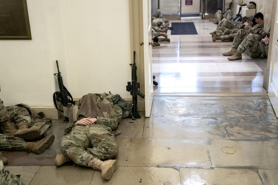 WASHINGTON, DC - JANUARY 13: Members of the National Guard rest in the U.S. Capitol on January 13, 2021 in Washington, DC. Security has been increased throughout Washington following the breach of the U.S. Capitol last Wednesday, and leading up to the Presidential inauguration. (Photo by Stefani Reynolds/Getty Images)