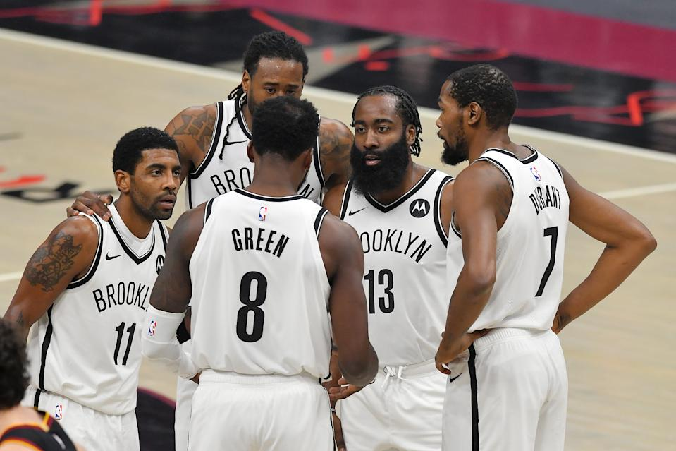 Kyrie Irving, DeAndre Jordan, Jeff Green, James Harden and Kevin Durant huddle on the court during a game.