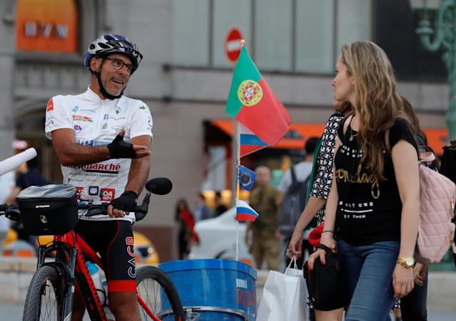 Portuguese cyclist Helder Batista, who arrived in Russia's capital to attend the 2018 FIFA World Cup, talks to pedestrians in central Moscow, Russia June 18, 2018. REUTERS/Tatyana Makeyeva