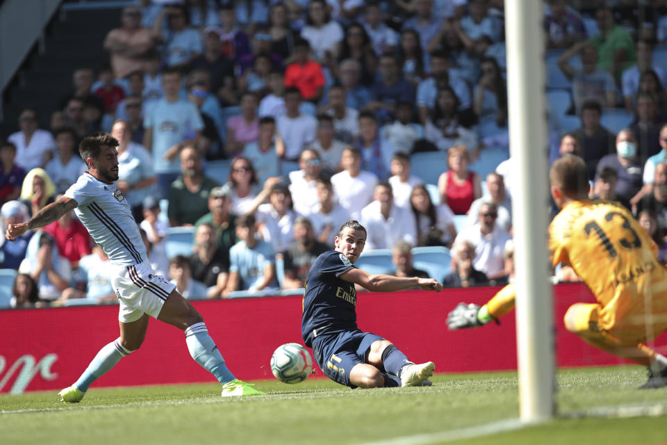 Real Madrid's Gareth Bale, centre, slides in to connect with the ball during La Liga soccer match between Celta and Real Madrid at the Balados Stadium in Vigo, Spain, Saturday, Aug. 17, 2019. (AP Photo/Luis Vieira)