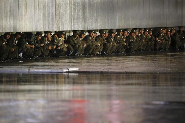 <p>North Korean officers shield themselves from the rain after the parade celebrating the 70th anniversary of the founding of the ruling Workers' Party of Korea, in Pyongyang, North Korea, Oct. 10, 2015. (Damir Sagolj/Reuters) </p>