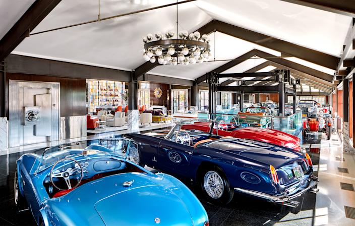 A light-blue 1964 Shelby Cobra, a dark-blue 1960 Ferrari, and a red 1955 Lancia are just three of the automotive treasures housed here. Custom polished nickel-and-bronze chandelier by Dank Fink Studio.