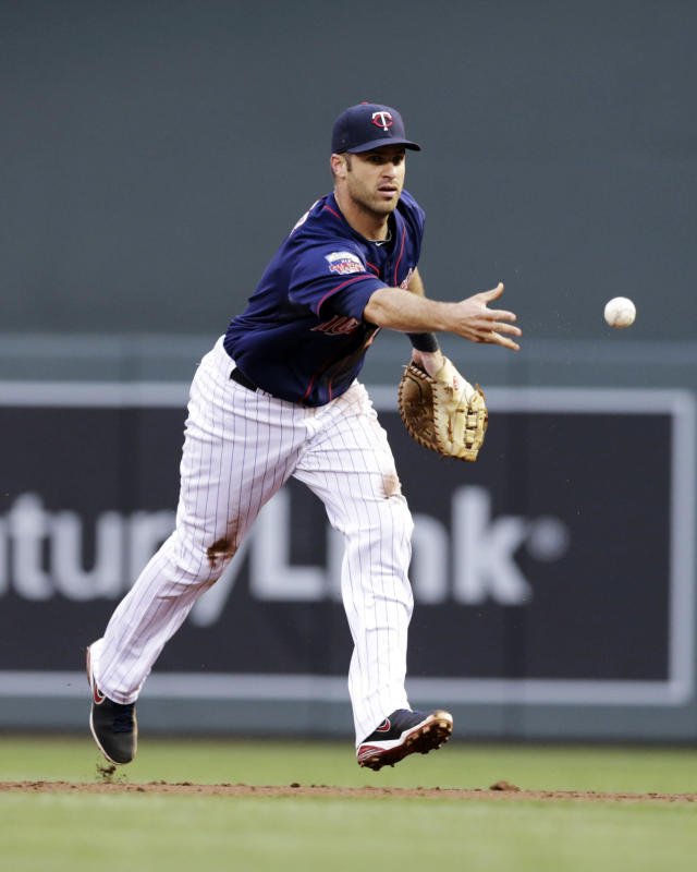 Minnesota Twins' Joe Mauer tosses the ball to pitcher Phil Hughes covering first for the out after making a diving stop of a ground ball by Texas Rangers' Adrian Beltre in the third inning of a baseball game Tuesday, May 27, 2014, in Minneapolis. B (AP Photo/Jim Mone)