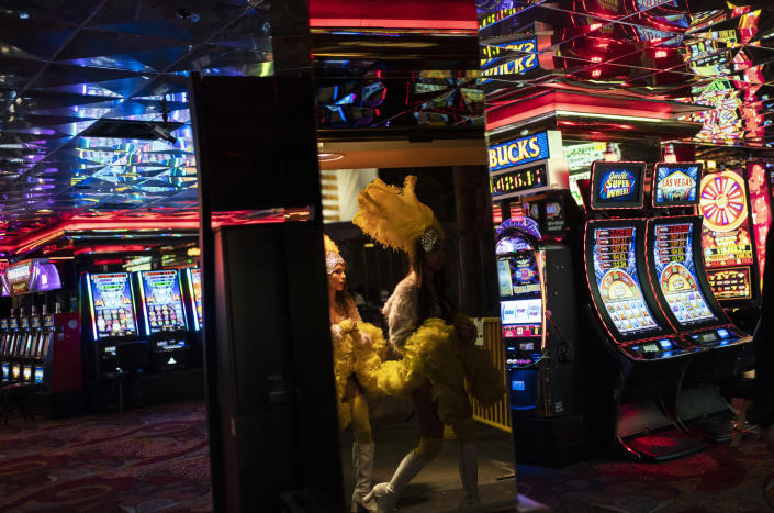 FILE - In this Feb. 10, 2021, file photo, buskers dressed as showgirls walk into a casino along the Las Vegas Strip in Las Vegas. Vaccinated diners, dancers, business owners and bodybuilders will be among those who can go maskless beginning June 1 in the Las Vegas area. County lawmakers on Tuesday, May 18, 2021, adopted Centers for Disease Control and Prevention guidelines and dropped plans to tie business occupancy to COVID-19 vaccination rates. (AP Photo/John Locher, File)