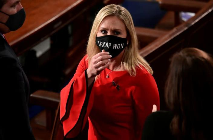 "FILE PHOTO: U.S. Rep. Marjorie Taylor Greene (R-GA) wears a ""Trump Won"" face mask as she arrives to take her oath of office as a member of the 117th Congress in Washington"