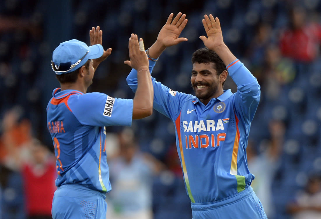Indian cricketer Ravindra Jadeja (R) celebrates with teammate Suresh Raina after dismissing Sri Lankan cricket team captain Angelo Mathews during the sixth match of the Tri-Nation series between India and Sri Lanka at the Queen's Park Oval stadium in Port of Spain on July 9, 2013. Sri Lanka is given a target of 178-runs to win after the rain interrupted match was tailored down to 26 overs. AFP PHOTO/Jewel Samad