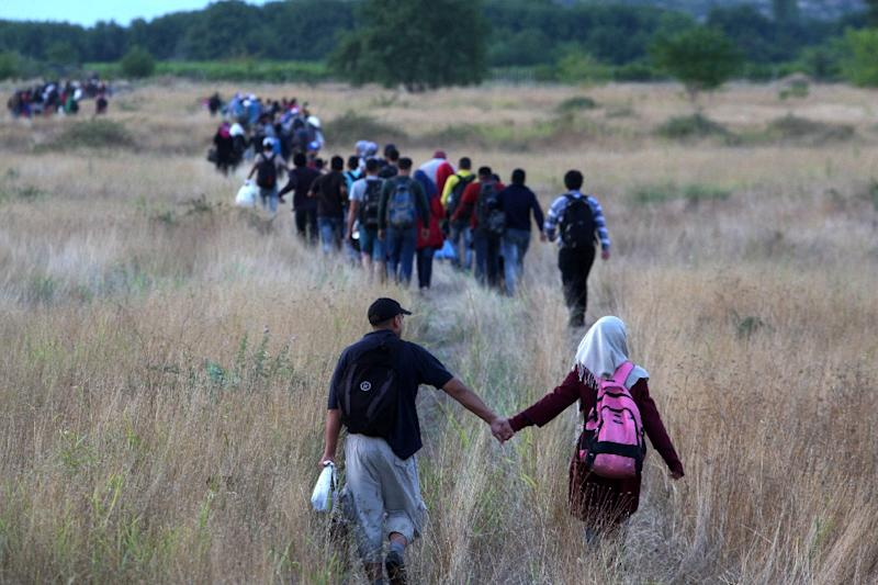 Migrants pass through the border from Greece into Macedonia near the town of Idomeni, Northern Greece, on August 22, 2015 (AFP Photo/Sakis Mitrolidis)
