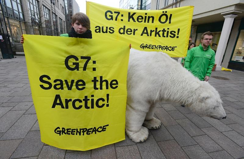 "Greenpeace activists pose with a mockup of a polar bear and with banners reading ""G7: Save the Arctic!"" and ""G7: No Oil from the Arctic!"" as they demonstrate in Luebeck, northern Germany, on April 14, 2015 (AFP Photo/John MacDougall)"