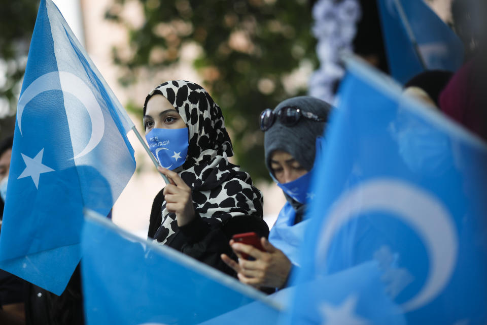 Uyghurs women take part in a protest during the visit of Chinese Foreign Minister Wang Yi in Berlin, Germany, Tuesday, Sept. 1, 2020. German Foreign Minister Heiko Maas meets his Chinese counterpart at the foreign ministry guest house Villa Borsig for bilateral talks. (AP Photo/Markus Schreiber)