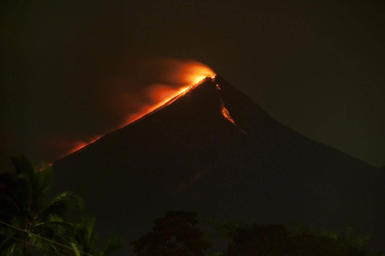 Lava flows from the Volcan de Fuego, or Volcano of Fire, as seen from the town of Palin, south of Guatemala City, late Thursday, Sept. 13, 2012. The long-simmering volcano exploded with a series of powerful eruptions outside one of Guatemala's most famous tourist attractions on Thursday, hurling thick clouds of ash and spewing rivers of lava down its flanks. (AP Photo/Moises Castillo)