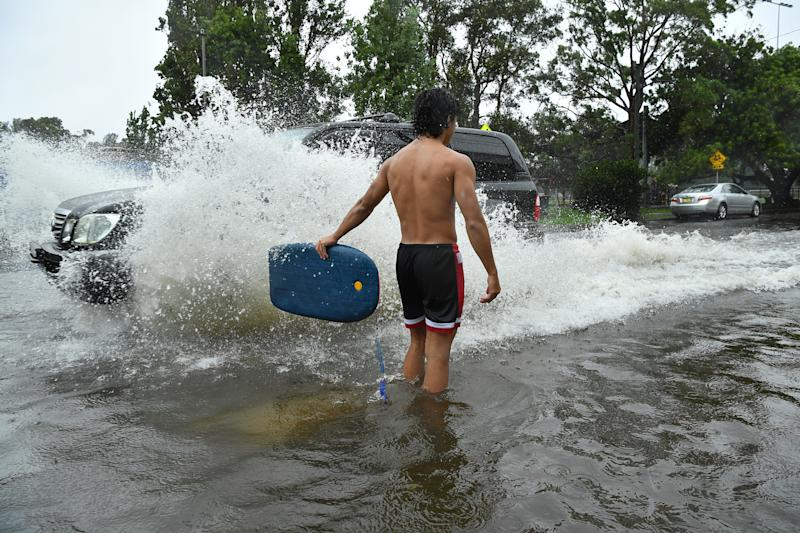 A group of boys direct traffic through floodwater at Tempe in Sydney. Source: AAP
