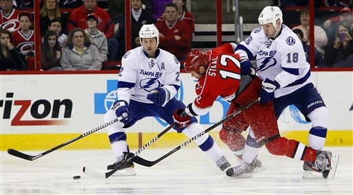 Carolina Hurricanes' Eric Staal (12) shoots the puck after colliding with Tampa Bay Lightning's Adam Hall (18) as Lightnings' Ryan Shannon (22) defends during the first period of an NHL hockey game in Raleigh, N.C., Saturday, March 3, 2012. (AP Photo/Karl B DeBlaker)