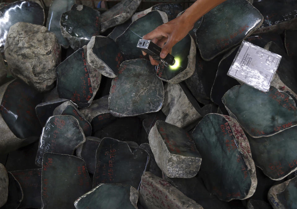FILE - In this Nov. 13, 2018, file photo, a merchant examines a jade stone displayed at the Gems Emporium in Naypyitaw, Myanmar. In its latest targeted sanctions against Myanmar's military, the U.S. has focused on an army controlled gems business rife with corruption and abuses that is part of one of the junta's most important sources of revenue. (AP Photo/Aung Shine Oo, File)