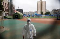 Security staff in a personal protection suit approaches the photographer at a testing site at the Guangan Sport Center after an unexpected spike of cases of the coronavirus disease (COVID-19) in Beijing