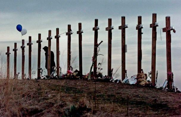 PHOTO: On April 28, 1999, a woman looks at crosses posted on a hill above Columbine High School in Littleton, Colo., in remembrance of the people who died during a shooting rampage at the school. (Eric Gay/AP, FILE)