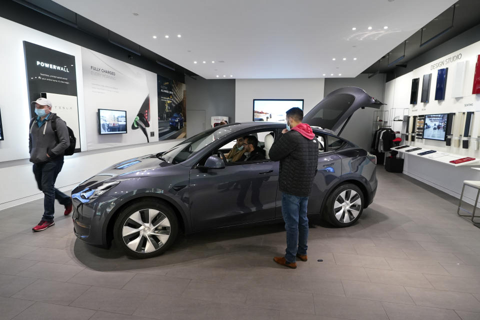 A Tesla Model Y Long Range is displayed at the Tesla Gallery on Feb. 24, 2021, in Troy, Mich. Opinion polls show that most Americans would consider an EV if it cost less, there were more charging stations along freeways, and if automakers offered a bigger variety of models. (AP Photo/Carlos Osorio)