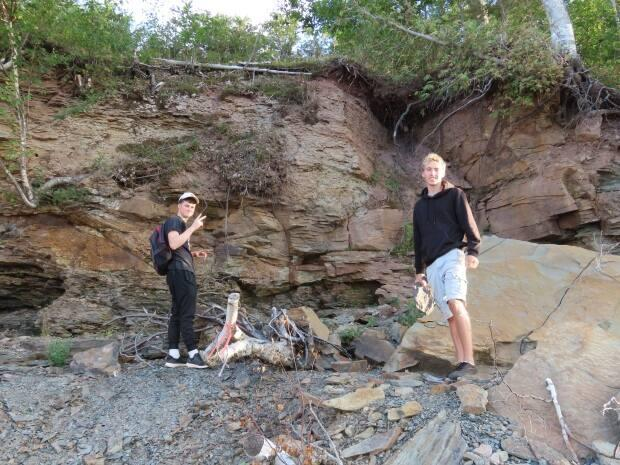 The cliffs and shoreline of Grand Lake are prime fossil hunting grounds for Rowan Norrad, left, and Luke Allen.