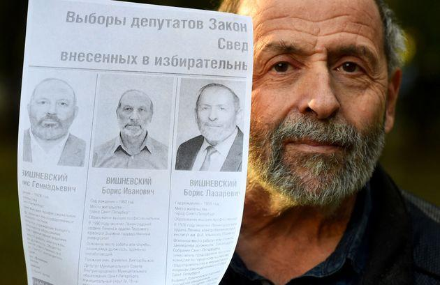 Boris Vishnevsky, a 65-year-old member of the liberal Yabloko party running for re-election to the regional parliament in Saint Petersburg, poses with a printed image of a mockup of an official election poster featuring nearly identical photos of him and two other Boris Vishnevskys side by side in Saint Petersburg on September 6, 2021 (Photo by OLGA MALTSEVA/AFP via Getty Images) (Photo: OLGA MALTSEVA via Getty Images)