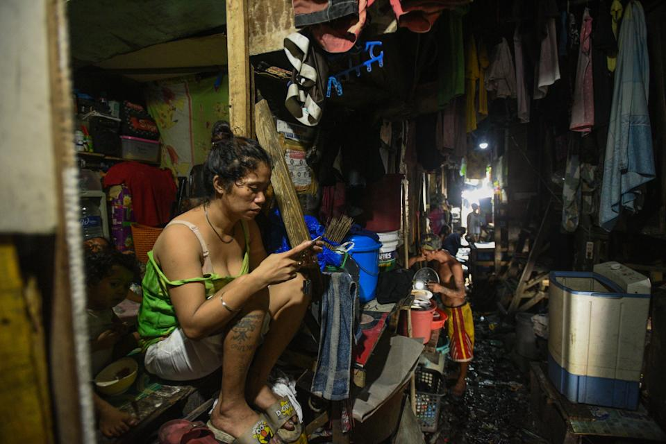This photo taken on March 18, 2020 shows a woman checking her phone outside her home in Manila. - Asian nations have imposed increasingly heavy measures to fight the outbreak of the COVID-19 coronavirus, the Philippines has ordered half its population of some 110 million to stay home. (Photo by Maria TAN / AFP) / TO GO WITH Health-virus-Philippines-poverty,FOCUS by Joshua Melvin and Ron Lopez (Photo by MARIA TAN/AFP via Getty Images)