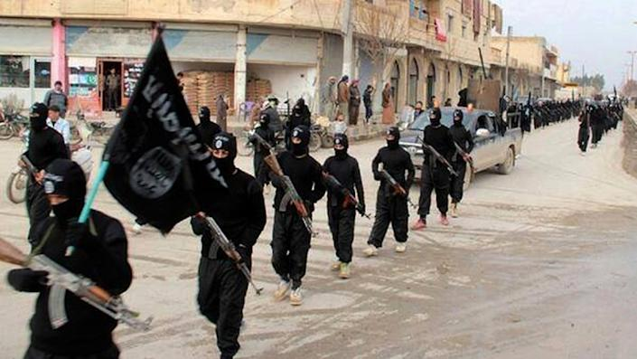 """CLICK IMAGE for slideshow: This undated file image posted on a militant website on Tuesday, Jan. 14, 2014, which has been verified and is consistent with other AP reporting, shows fighters from the al-Qaida linked Islamic State of Iraq and the Levant (ISIL), now called the Islamic State group, marching in Raqqa, Syria. U.S. President Barack Obama on Wednesday, Sept. 10, 2014 ordered the United States into a broad military campaign to """"degrade and ultimately destroy"""" militants in two volatile Middle East nations, authorizing airstrikes inside Syria for the first time, as well as an expansion of strikes in Iraq. (AP Photo/Militant Website, File)"""