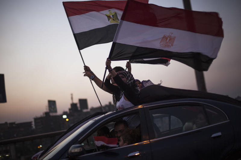 """Supporters of the Tamarrod or """"Rebe""""l movement wave Egyptian flags in Cairo, Egypt, Sunday 7, 2013 . Egypt's new leadership wrangled over the naming of a prime minister, as both the Muslim Brotherhood and their opponents called for new mass rallies Sunday, renewing fears of another round of street violence over the military's ousting of Islamist President Mohammed Morsi. The calls for competing rallies come after clashes two days ago between the rival camps left at least 36 dead and more than 1,000 injured nationwide. (AP Photo/Manu Brabo)"""