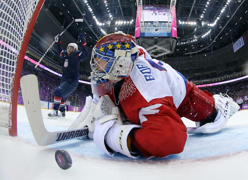 USA forward Phil Kessel reacts as Russia goaltender Sergei Bobrovski can't stop a goal by USA defenseman Cam Fowler during the second period of a men's ice hockey game at the 2014 Winter Olympics, Saturday, Feb. 15, 2014, in Sochi, Russia. (AP Photo/Bruce Bennett, Pool)