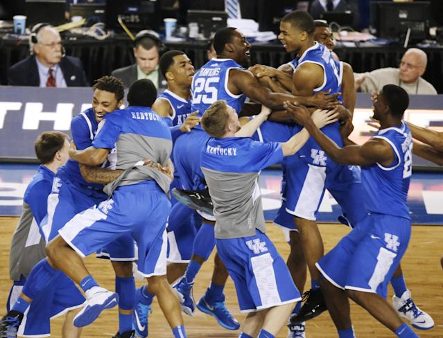 Kentucky celebrates after guard Aaron Harrison made a three-point basket in the final seconds against Wisconsin to win the game 74-73 during their NCAA Final Four tournament college basketball semifinal game Saturday, April 5, 2014, in Arlington, Texas. (AP Photo/Tony Gutierrez)