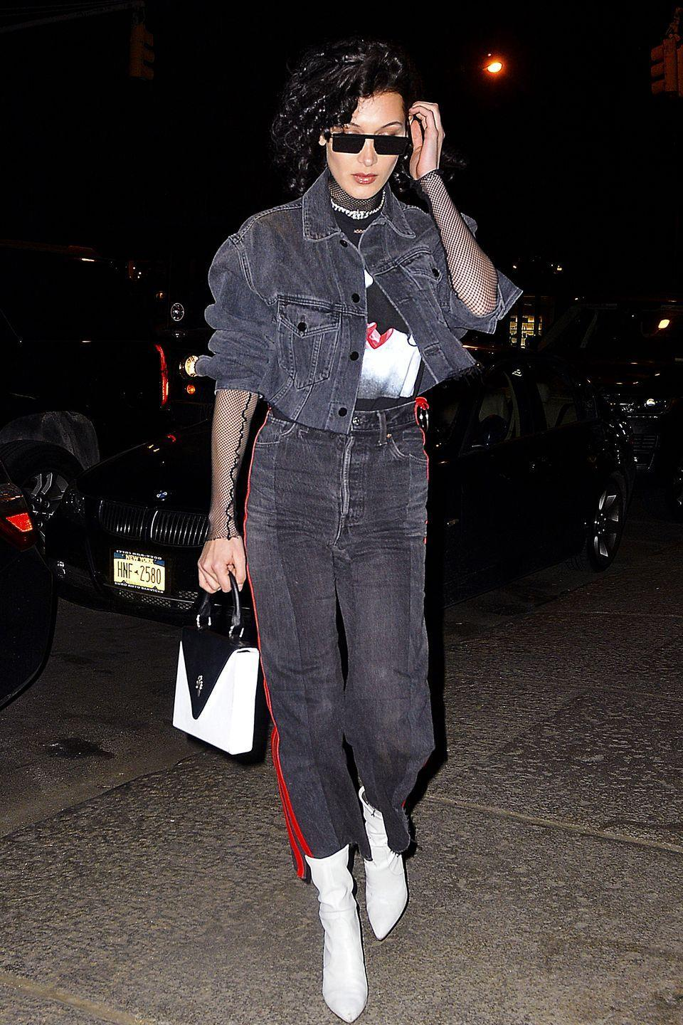 <p>In a sheer fishnet top under a graphic tee and grey Alexander Wang denim jacket with red leather-lined Vetements jeans, Stuart Weitzman boots, a Chrome Hearts bag and black sunglasses while out in New York City. </p>