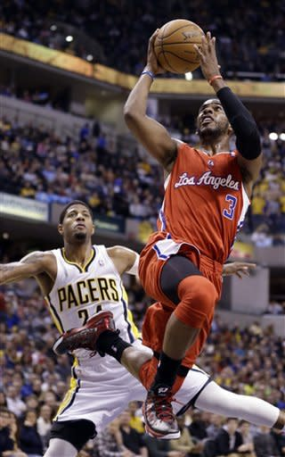 Los Angeles Clippers guard Chris Paul, right, shoots in front of Indiana Pacers' Paul George in the first half of an NBA basketball game in Indianapolis, Thursday, Feb. 28, 2013. (AP Photo/Michael Conroy)