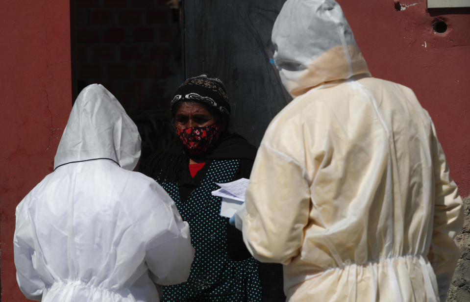 Healthcare workers dressed in full protective gear interview a resident during a house-to-house campaign against the spread of the new coronavirus, in the Mallasa neighborhood of La Paz, Bolivia, Saturday, Aug. 8, 2020. (AP Photo/Juan Karita)