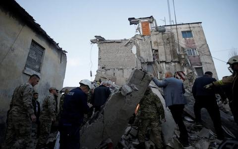 <span>Emergency personnel work near a damaged building in Thumane</span> <span>Credit: REUTERS </span>
