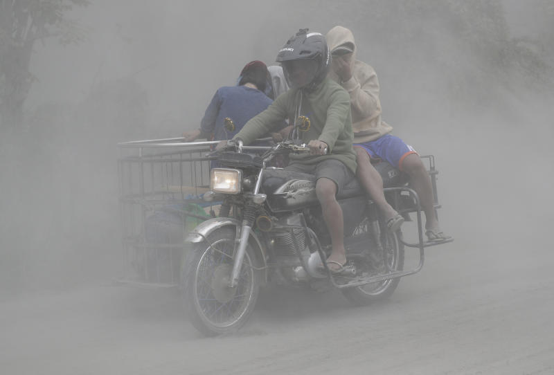 In this Jan. 13, 2020, photo,  a family rides their motorcycle through clouds of ash as they evacuate to safer grounds as Taal volcano in Tagaytay, Cavite province, southern Philippines. Red-hot lava is gushing from the volcano after a sudden eruption of ash and steam that forced residents to flee and shut down Manila's airport, offices and schools. (AP Photo/Aaron Favila)