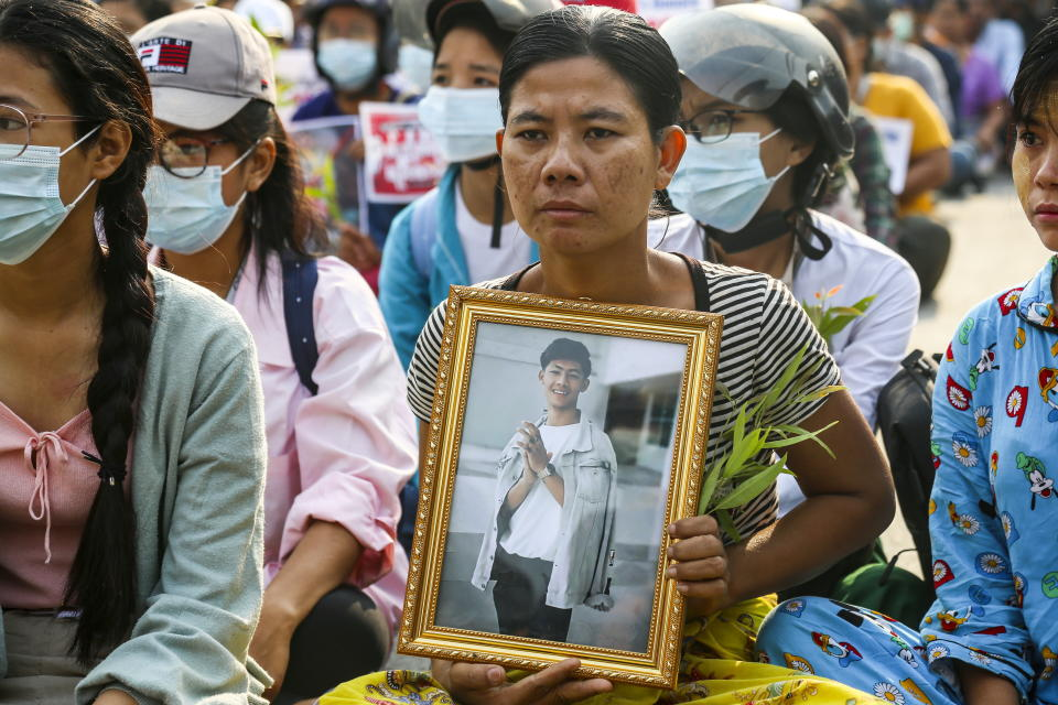 A mum is shown holding a portrait of her son who died during a protest against the military coup in Myanmar. Source: AAP