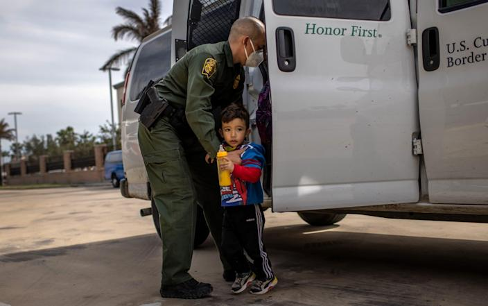 A US Border Patrol agent delivers a young asylum seeker and his family to a bus station in Brownsville, Texas - John Moore/Getty Images North America