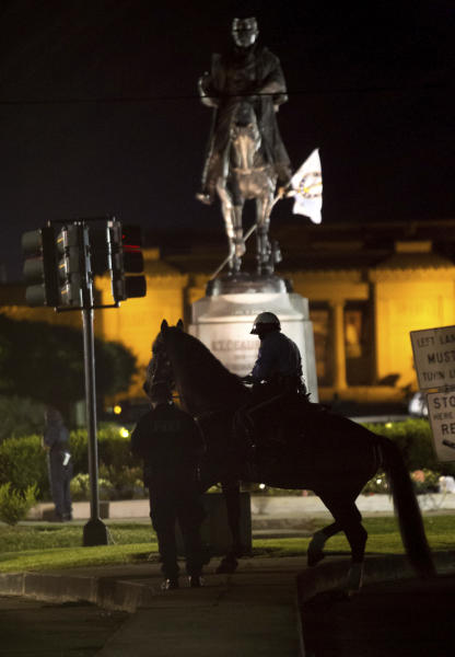 A New Orleans Police mounted patrol circles the statue of Confederate Gen. P.G.T. Beauregard as the statue is prepared for removal from the entrance to City Park in New Orleans, Tuesday, May 16, 2017. The removal of the statue comes after the city has already taken down a statue of Jefferson Davis, the Confederacy's only president, and a memorial to a white rebellion against a biracial Reconstruction-era government in the city. (AP Photo/Scott Threlkeld)
