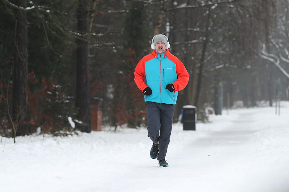 A man jogs down a snow covered street in Catterick, North YorkshirePA