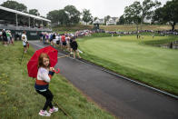 A child holds an umbrella while spectators watch Phil Mickelson, Bubba Watson, and Paul Casey play the 17th green during the second round of the Travelers Championship golf tournament at TPC River Highlands, Friday, June 25, 2021, in Cromwell, Conn. (AP Photo/John Minchillo)
