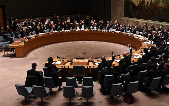 UN Security Council votes to adopt the resolution as it holds its first-ever meeting of finance ministers, on December 17, 2015 (AFP Photo/Timothy A. Clary)