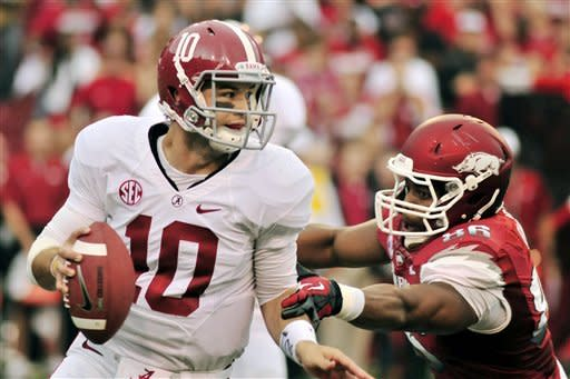 Alabama quarterback AJ McCarron (10) looks for a receiver as he is pressured by Arkansas defensive end Trey Flowers (86) during the first half of an NCAA college football game in Fayetteville, Ark., Saturday, Sept. 15, 2012. (AP Photo/April L. Brown)
