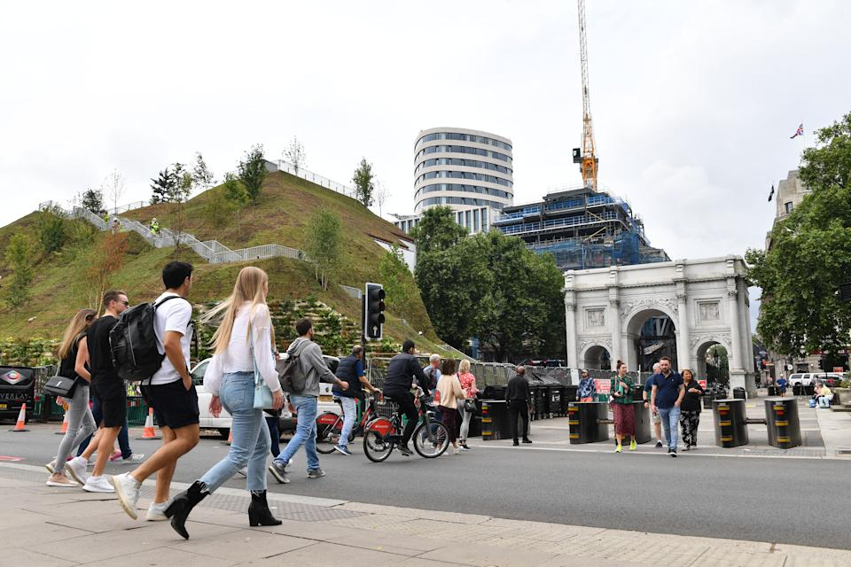 People cross the road next to the Marble Arch Mound, a new temporary attraction, next to Marble Arch in central London on July 25, 2021. - Designed by Dutch architecture company MVRDV, the 25-metre-high landscaped Marble Arch Mound consists of a stairway leading through trees and greenery to a viewing platform at the top. The ticketed new attraction opens to the public on July 26. (Photo by JUSTIN TALLIS / AFP) (Photo by JUSTIN TALLIS/AFP via Getty Images)