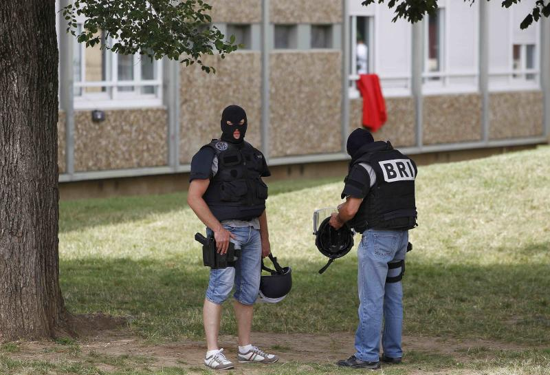 French special Police forces stand guard in front of a residential building during a raid in Saint-Priest