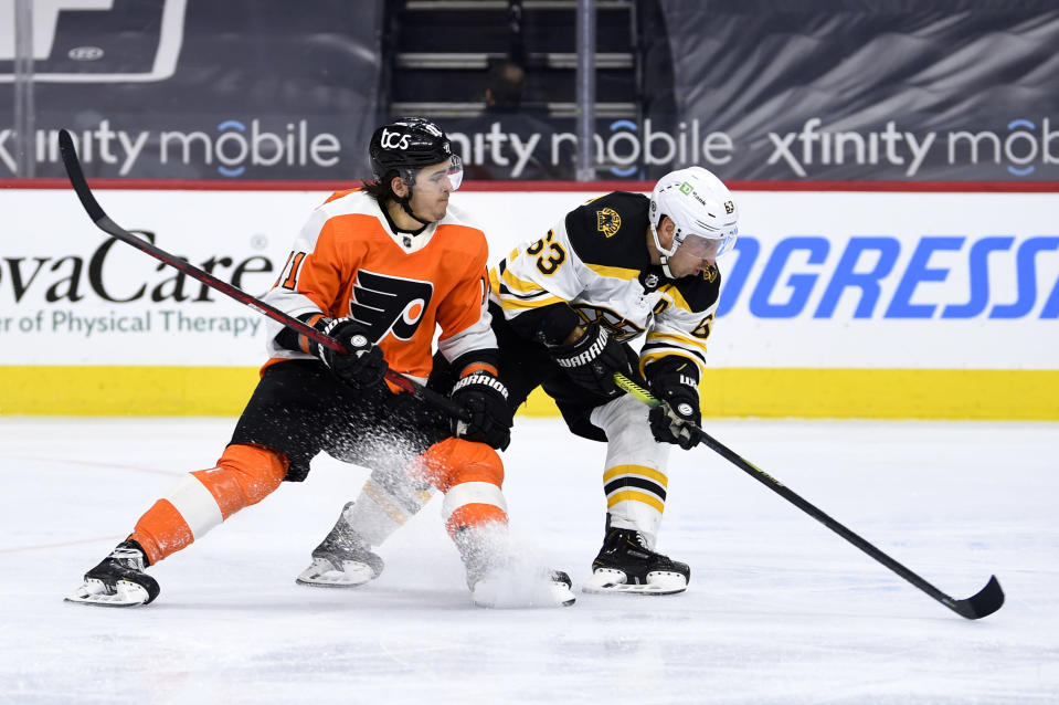 Boston Bruins' Brad Marchand, right, and Philadelphia Flyers' Travis Konecny chase the puck during the third period of an NHL hockey game, Tuesday, April 6, 2021, in Philadelphia. The Bruins won 4-2. (AP Photo/Derik Hamilton)