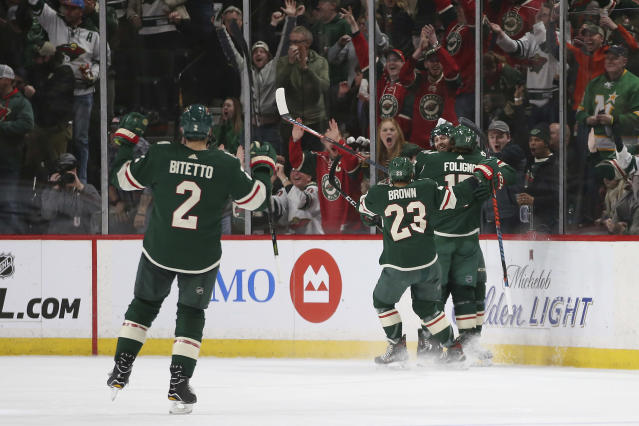 Minnesota Wild's Marcus Foligno and J.T. Brown celebrate with teammate Eric Fehr after Fehr scored the team's first goal during the second period of an NHL hockey game against the Nashville Predators, Sunday, March 3, 2019, in St. Paul, Minn. (AP Photo/Stacy Bengs)