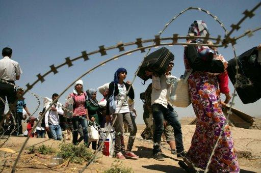 Syrian refugees cross the border into the autonomous Kurdish region of northern Iraq, on August 17, 2013