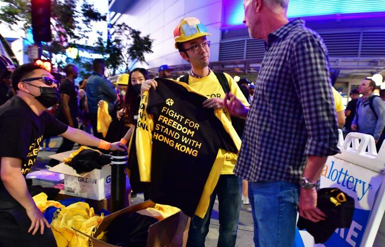 Supporters of Hong Kong's pro-democracy protesters distribute free t-shirts outside the Staples Center ahead of the Lakers vs Clippers NBA season opener (AFP Photo/Frederic J. BROWN)