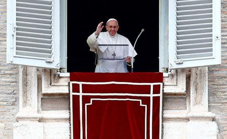 Pope Francis waves as he leads the Angelus prayer in Saint Peter's square at the Vatican