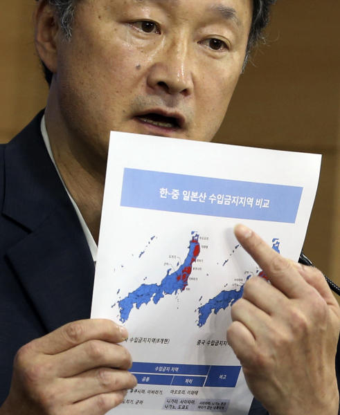 """Son Jae-hak, vice minister of South Korean Maritime Affairs and Fisheries, shows a document showing Japanese prefectures with import bans imposed by South Korea and China respectively during a press conference to announce the government's ban on the imports of fisheries products from Japan's Fukushima Prefecture in Seoul, South Korea, Friday, Sept. 6, 2013. South Korea announced Friday that it was banning all fish imports from Japan's Fukushima region because of what officials called a growing public worry over radiation contamination that has reportedly prompted a sharp decline in fish consumption. The letters at top read """" Import bans imposed by South Korea and China respectively."""" (AP Photo/Yonhap, Jo Bo-hee) KOREA OUT"""