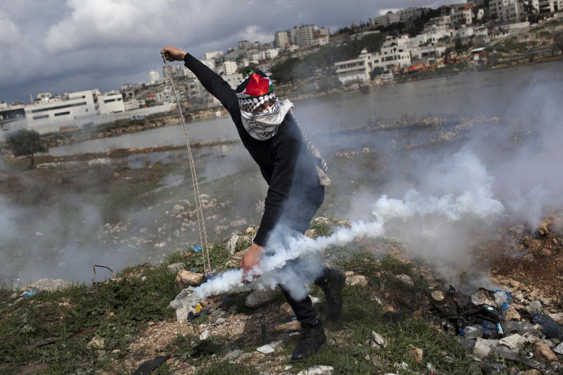 A masked Palestinian throws back a gas canister previously shoot by Israeli forces, not pictured, during a protest to support Palestinian prisoners, outside Ofer, an Israeli military prison near the West Bank city of Ramallah, Tuesday, Feb. 19, 2013. Palestinian protesters clashed with Israeli soldiers at a rally Tuesday in support of four imprisoned Palestinians on hunger strike, as hundreds of inmates said they were refusing food for the day in solidarity with the fasting inmates. One of the four hunger-striking Palestinians is 35-year-old Samer Issawi whose health has severely deteriorated after he has refused food, on-and-off, for more than 200 days. (AP Photo/Bernat Armangue)