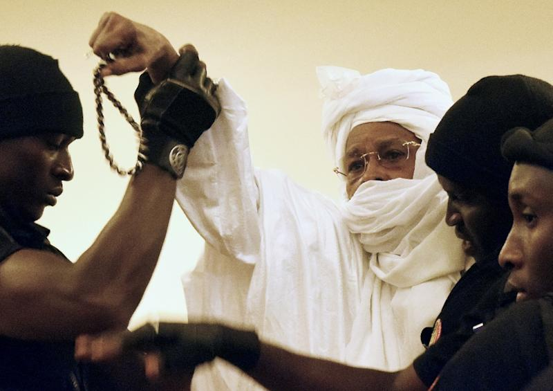 Former Chadian dictator Hissene Habre (C) is escorted by prison guards into the courtroom for the first proceedings of his trial by the Extraordinary African Chambers in Dakar on July 20, 2015. More than a quarter-century after his blood-soaked reign came to an end, former Chadian dictator Hissene Habre went on trial in a Senegalese court on July 20 in what is seen as a test case for African justice. AFP PHOTO / SEYLLOU (AFP Photo/Seyllou)